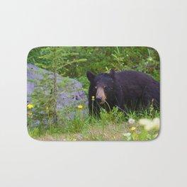 Black bear munches on some dandelions in Jasper National Park Bath Mat