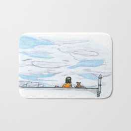 The little girl in orange. Watching the clouds pass over the sky Bath Mat