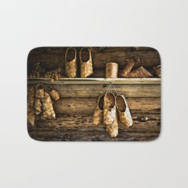 Medieval Bast Shoes On The Wooden Wall Bath Mat