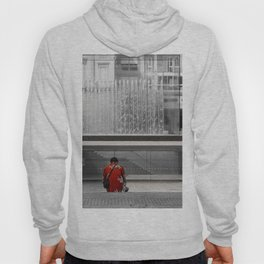 A man in a red shirt sits in front of a fountain Hoody