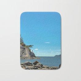 A lone figure on a cliff Bath Mat