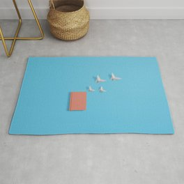 Orange notebook with butterflies flying out on blue Rug