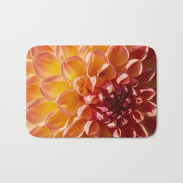 A Fiery colored Dahlia (Asteraceae) shines in the morning sun Bath Mat