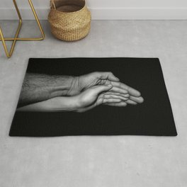 Father and child / Photograph of father and child hands pressed together Rug