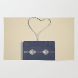 Retro black music cassette and heart shaped tape on beige background Rug