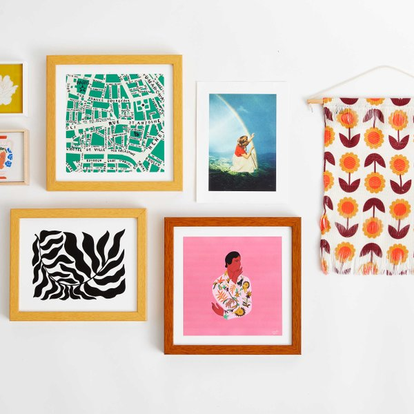 flatlay with framed prints and abstract wall hanging
