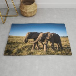 Two happy elephants walking together in African Savannah at sunset Rug