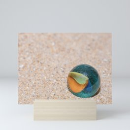 Glass marble with colored interior resting on the sand Mini Art Print