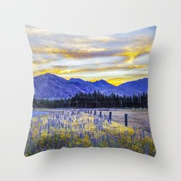 Magnificent glowing sunset over blue mountains and field flowers in New Zealand Throw Pillow