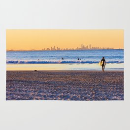 Surfer walks away from the sea on Coolangatta beach at sunset. Surfer's Paradise is in the backgroun Rug