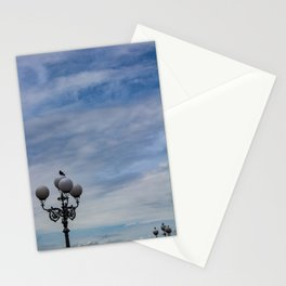 Large space of free sky and two small luminaries where a group of pigeons have posed. Stationery Cards