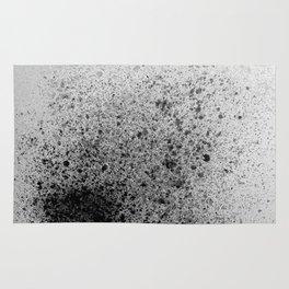 Black Spray Paint on Gray Rug