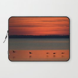A flock of geese flying north across the calm evening waters of the bay Laptop Sleeve