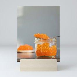 Macro shot of red caviar on jar on a gray background Mini Art Print