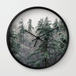 Tall ice covered evergreen trees fill the mountain tops Wall Clock