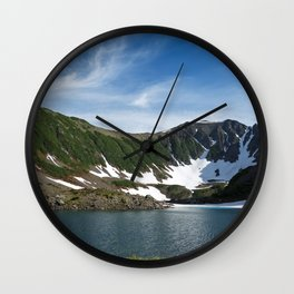 Stunning summer mountain landscape: Blue Lake, green forest on hillsides, blue sky on sunny day Wall Clock