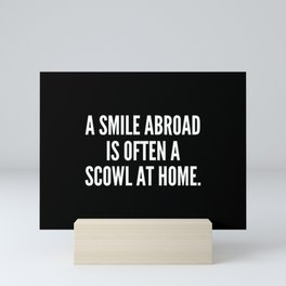 A smile abroad is often a scowl at home Mini Art Print
