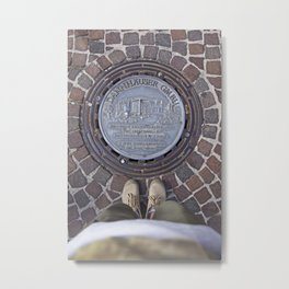 Man standing in front of a manhole Metal Print