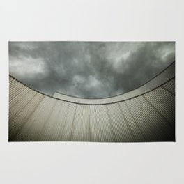 Building with metal covering against stormy sky Rug