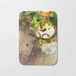 Olive oil,  herbs and spices on a wooden table Bath Mat