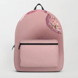 Pink doughnut with sprinkles falling or flying in motion against pink pastel background Backpack