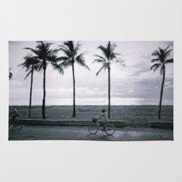 Cyclists by the beach Rug