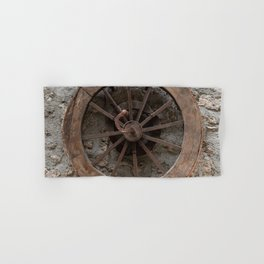 Wooden wheel hanging on a stone wall Hand & Bath Towel