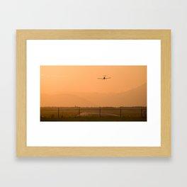 Light airplane landing at sunset on the summer solstice Framed Art Print