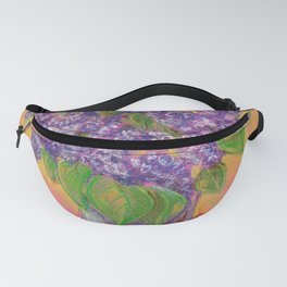 Bouquet of lilac flowers in a glass vase on an orange background Fanny Pack