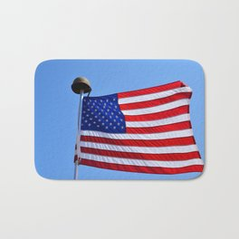 United States flag waving with a military helmet on the mast Bath Mat