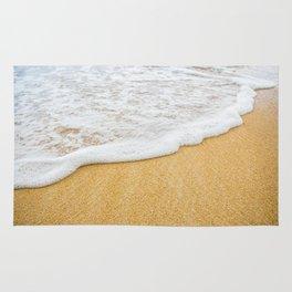 Foamy sea water is washing sandy beach Rug