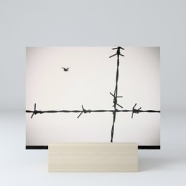Freedom, a seagull is flying totally free beyond a spiked wire. Mini Art Print