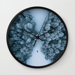 Man lying in the snow on a frozen lake in a winter forest - Landscape Photography Wall Clock