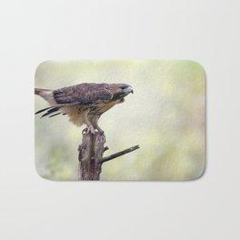 Red-tailed hawk  sitting on a log Bath Mat
