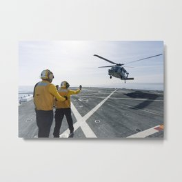On the top deck of the USS San Diego US Navy personnel monitor a helicopter landing after an Orion u Metal Print