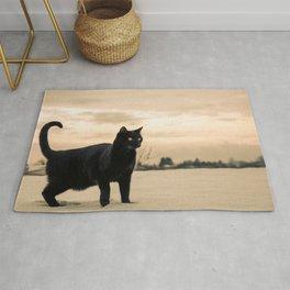 black cat portrait in a winter landscape Rug