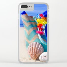 Beach bag with seashell, flip flops, rock and sunscreen by the ocean Clear iPhone Case