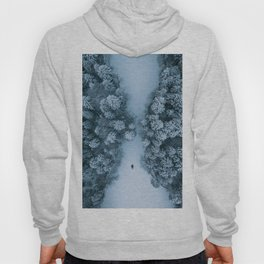 Man lying in the snow on a frozen lake in a winter forest - Landscape Photography Hoody