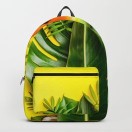 Tropical leaves and flowers on yellow background Backpack