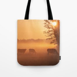 Rural idyll, grazing cows in the morning red Tote Bag