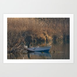 Fisherman on a boat by the river in the early morning Art Print