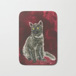 Grey kitten on a whine red background Bath Mat
