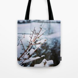 Early spring leaves covered by snow Tote Bag