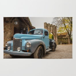 Historic blue-colored pickup parked in the streets of an historic Italian village Rug