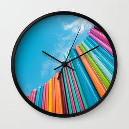 Colorful Rainbow Pipes Against Blue Sky Wall Clock