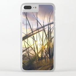 Sun light is coming through green grass in the sun set with sea in the behind and cloudy sky Clear iPhone Case