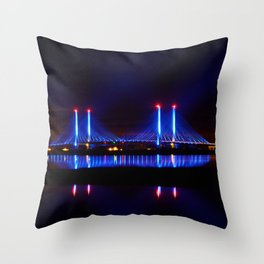 The Indian River Inlet bridge reflecting off the bay as beams of blue light penetrate the night sky Throw Pillow
