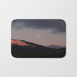 Moon over blackness and red pink ice Bath Mat