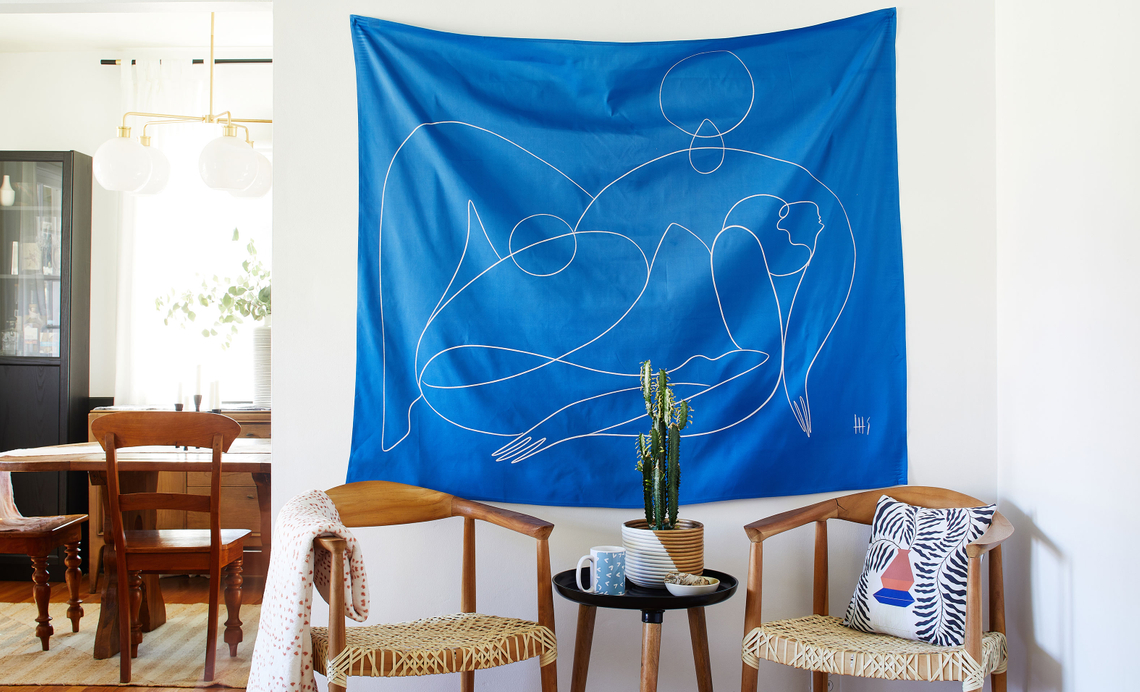 blue minimal line drawing tapestry hanging in a living room