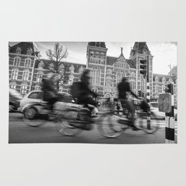 Cyclists ride in Amsterdam street in front of the Rijksmuseum Rug